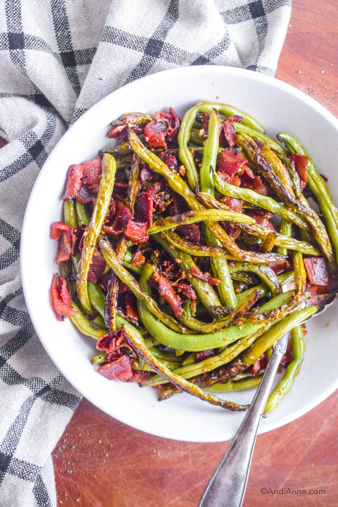 garlic green beans with bacon in a white serving dish with large silver spoon