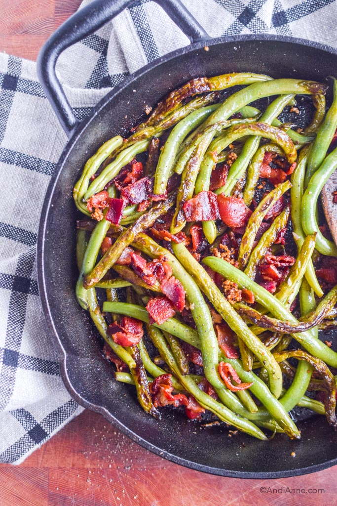 Cooked green beans and bacon in black skillet with plaid kitchen towel underneath