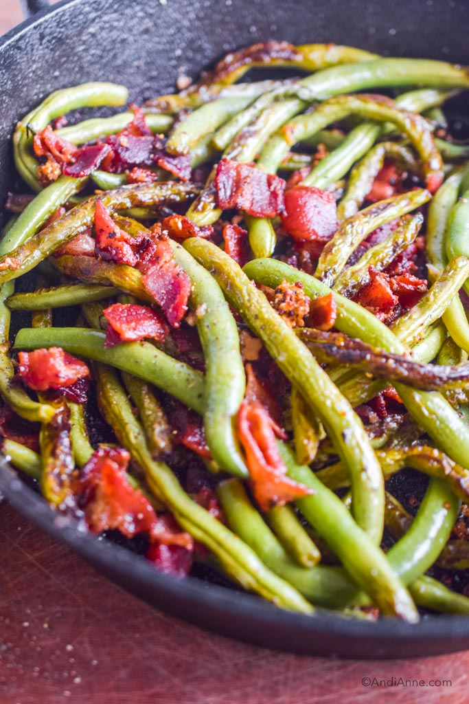 close up of cooked green beans and bacon in black frying pan
