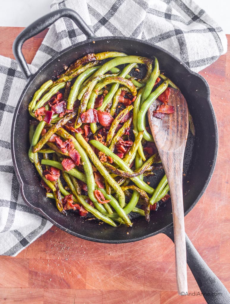 garlic green beans with bacon in a black skillet with wooden spoon and kitchen towel behind it