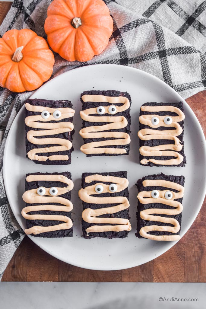 Halloween mummy chickpea brownies on a big white plate on wood block. Plaid kitchen towel and small pumpkins surround the plate.