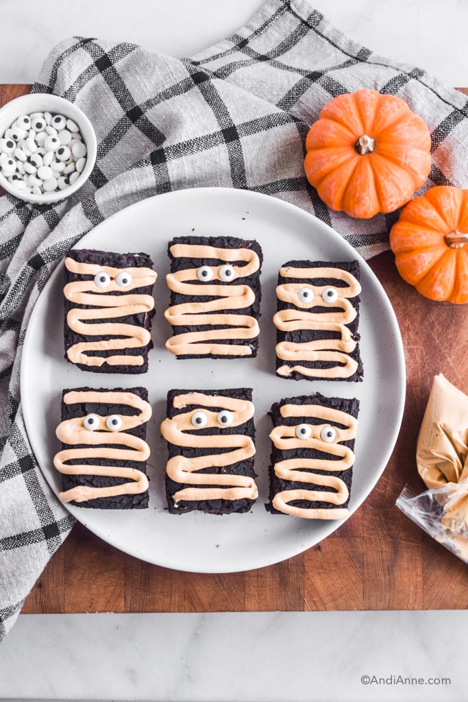 Looking down at the white plate of halloween brownies with two small pumpkins, a piping bag of light brown cream cheese icing, and a bowl of candy eyeballs, and a plaid kitchen towel surrounding the plate.