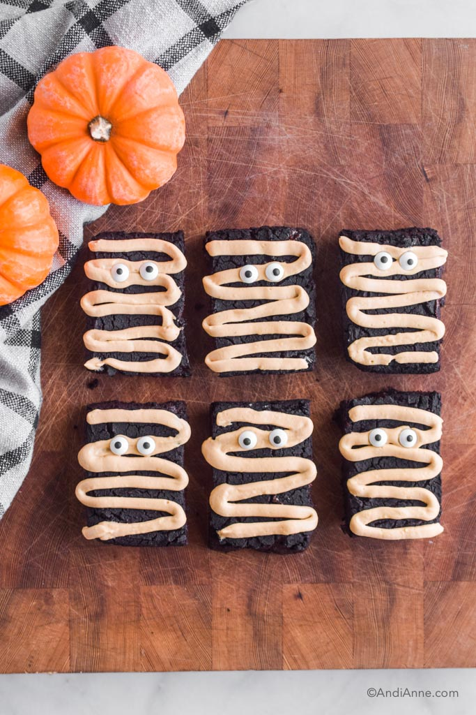 Six brownies with mummy designs on a wood butcher block with small pumpkins and kitchen towel on the left side.
