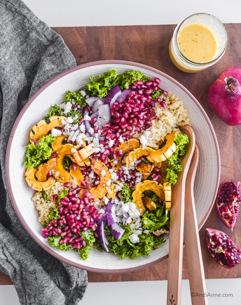 fall harvest salad in a white bowl with wooden spoons and pomegranate beside it