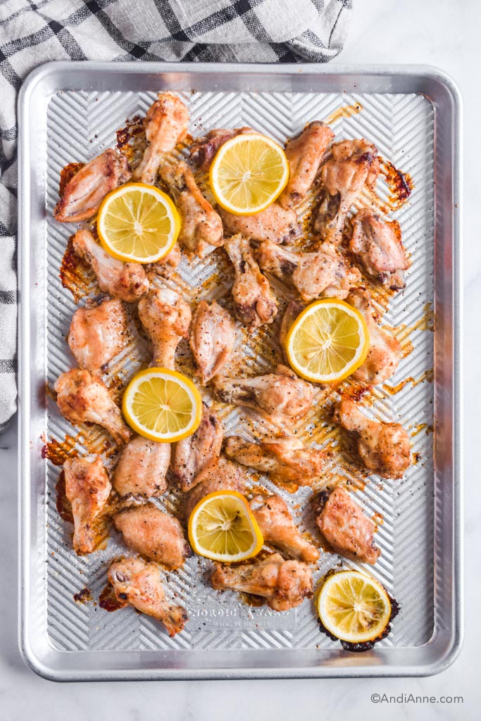 lemon garlic chicken wings on a silver baking sheet with sliced lemons