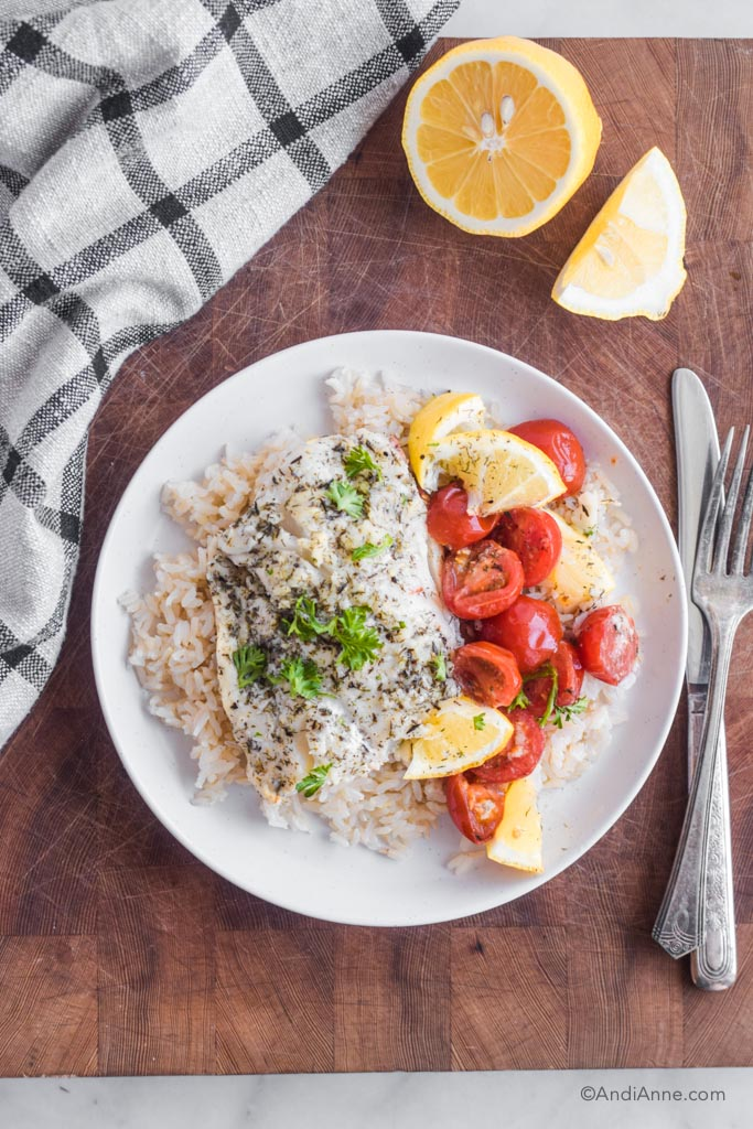 Baked cod, lemon wedges, and cherry tomatoes on top of a bed of rice on a white plate. Fork and knife beside it.