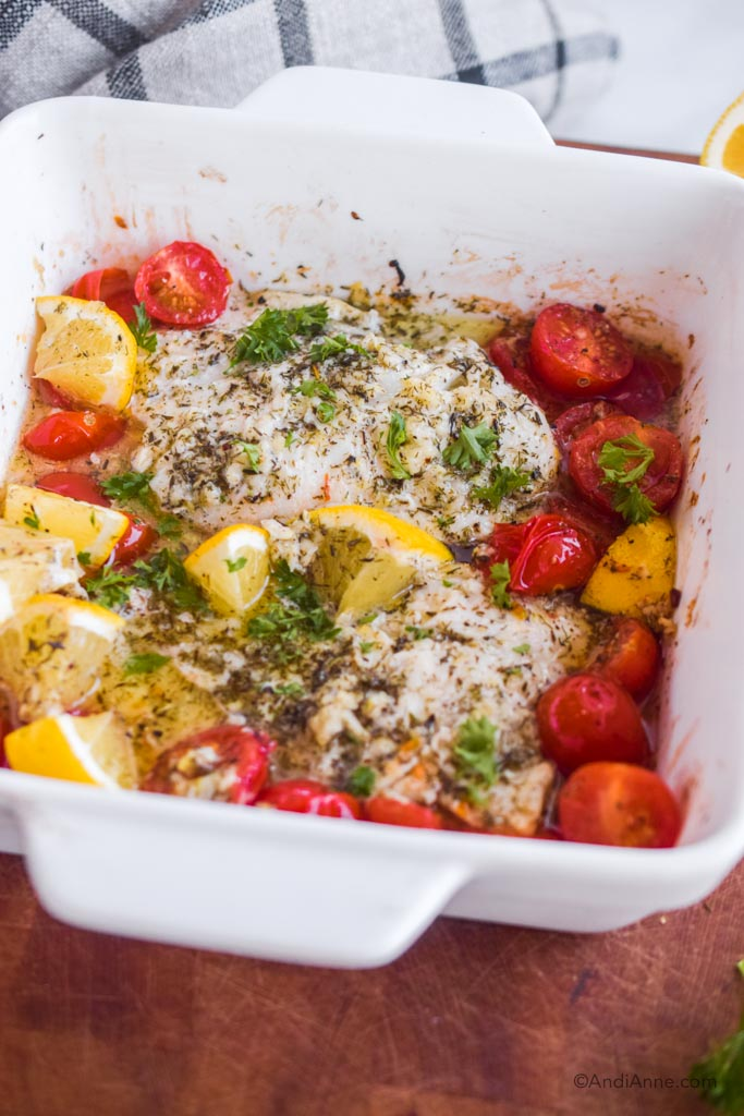 Side angle close up of white dish with baked cod, cherry tomatoes, and lemon slices. All coated in an herb dressing.