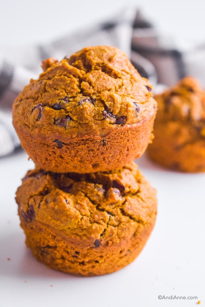 two stacked pumpkin chocolate chip muffins.