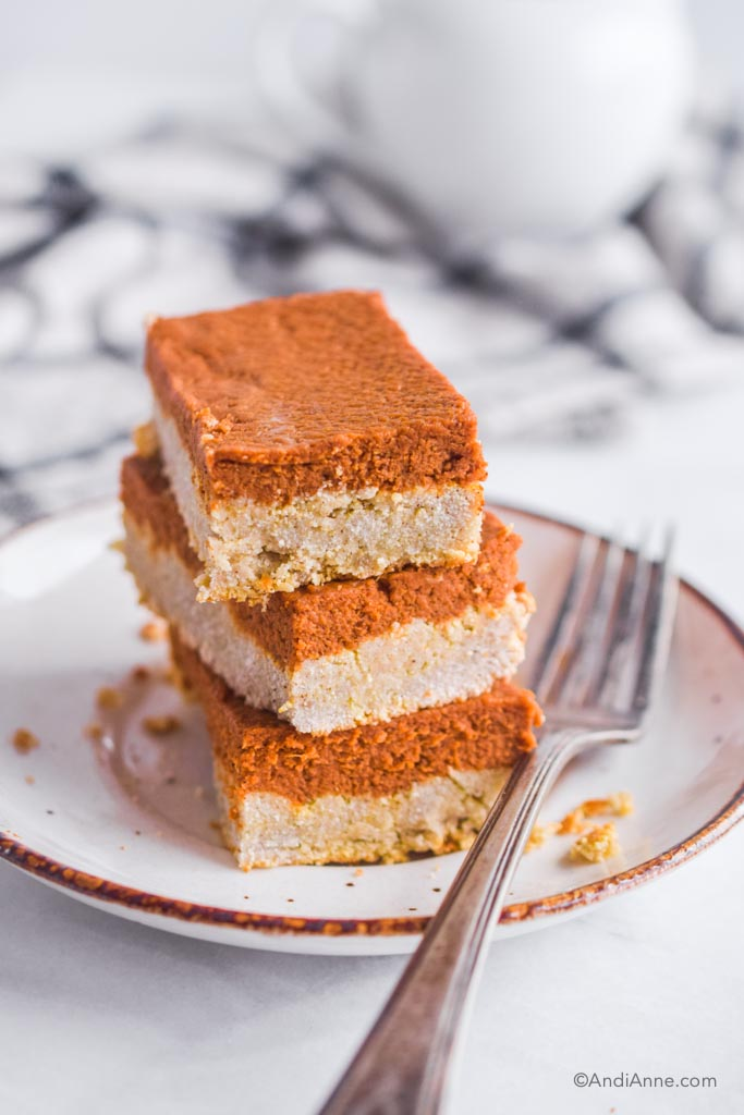 three pumpkin pie bars stacked on top of eachother on a white plate