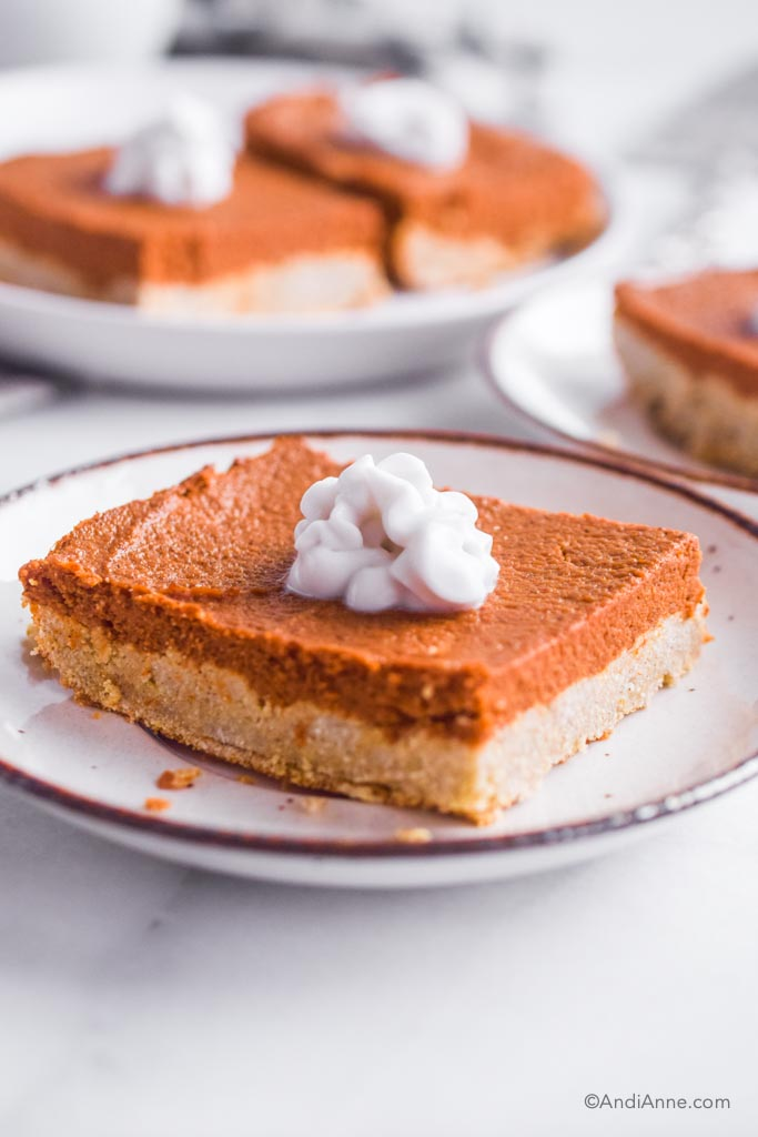 Side angle of pumpkin pie bars on white plate with dollop of whipped coconut cream on top