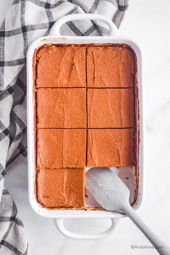 cooked and sliced pumpkin pie bars sitting in white baking dish. Grey spatula at the bottom with one slice removed.