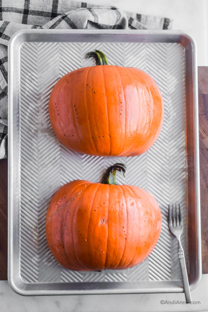pumpkin cut in half and poked with a fork lying face down on a baking sheet. Fork beside it.