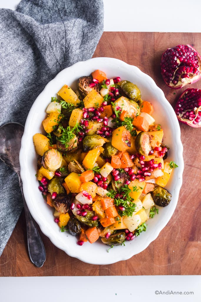 roasted root vegetables with pomegranate seeds in white serving dish on wood cutting board