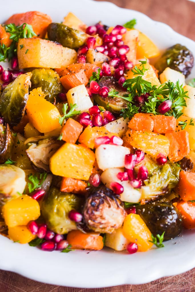close up of roasted root vegetables topped with pomegranate seeds and parsley