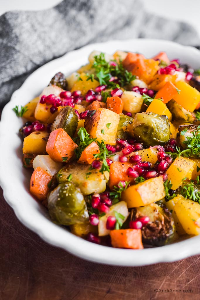 close up of white dish with roasted root vegetables, pomegranate seeds and parsley