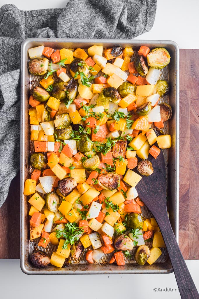Chopped roasted root vegetables on a baking sheet with wooden spatula on side.