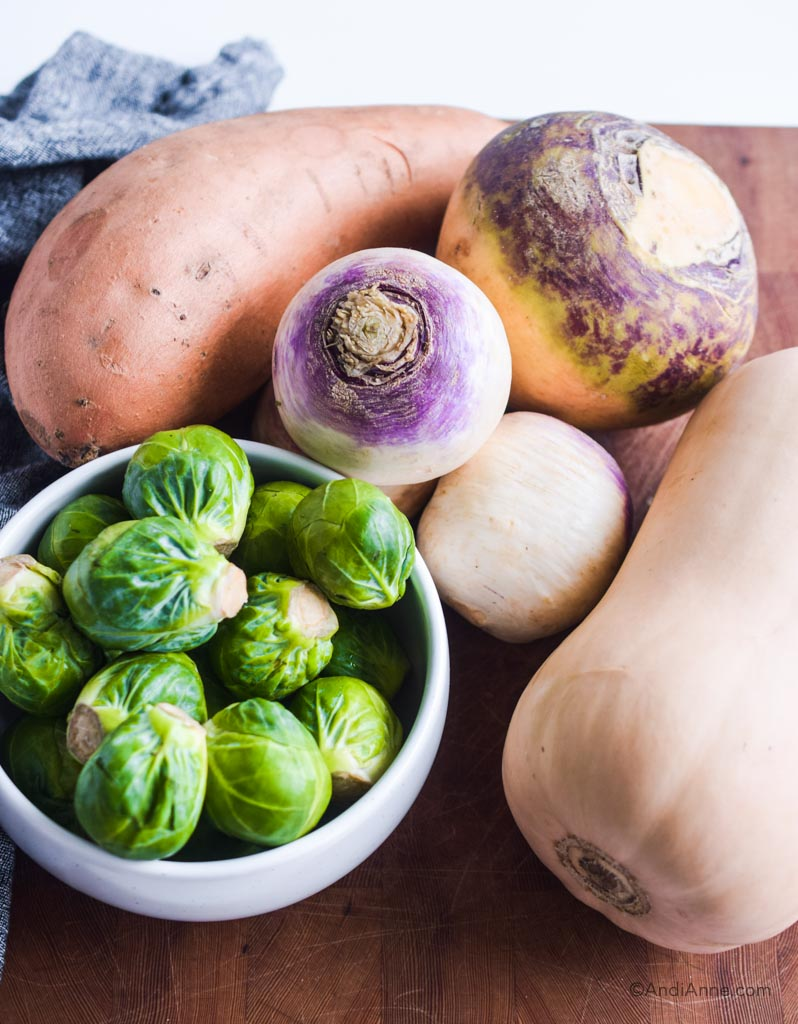 sweet potato, brussels sprouts, butternut squash, turnip and rutabaga on a wood cutting board.