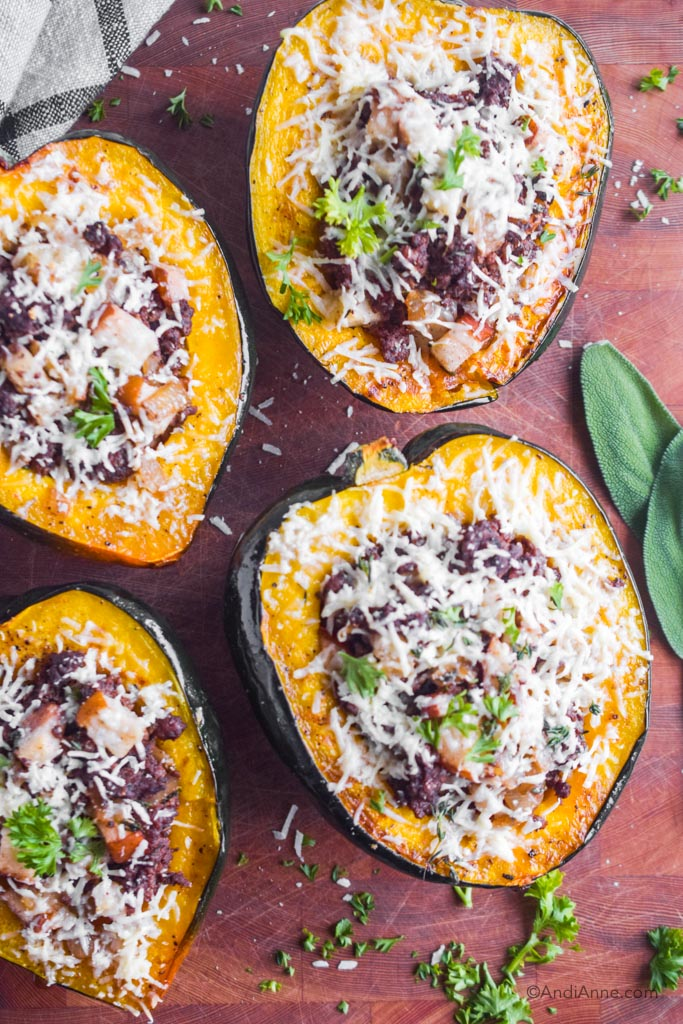 stuffed acorn squash with ground beef, pears and grated parmesan on a wood cutting board.