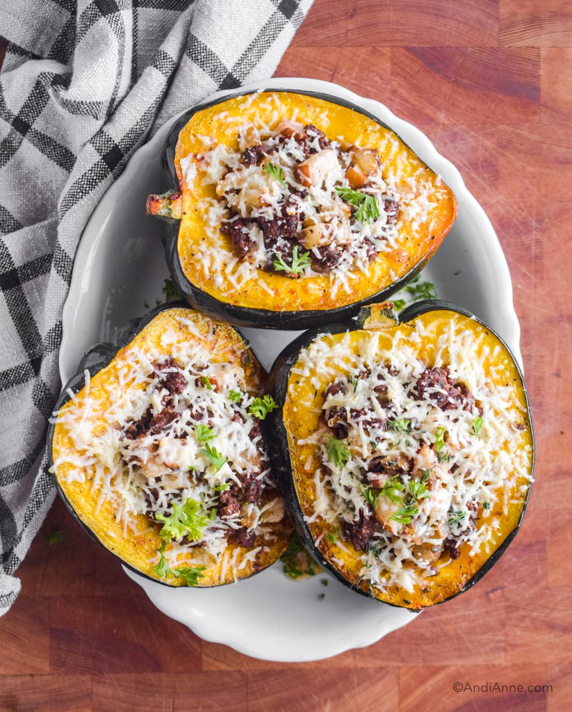 Three slices of stuffed acorn squash on a white plate