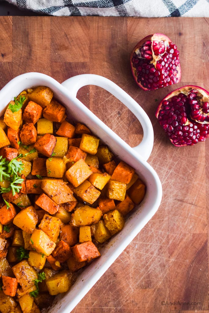 looking down on white tray of squash and sweet potato cubes in cinnamon. Open pomegranate is beside.