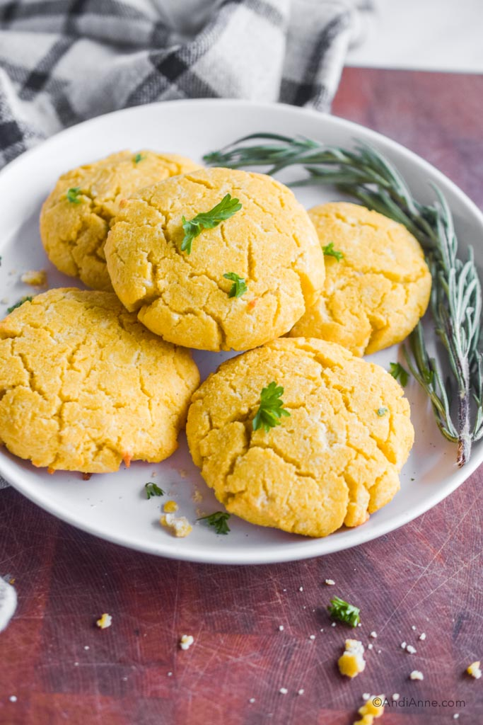 coconut flour biscuits on a white plate with fresh rosemary beside it.