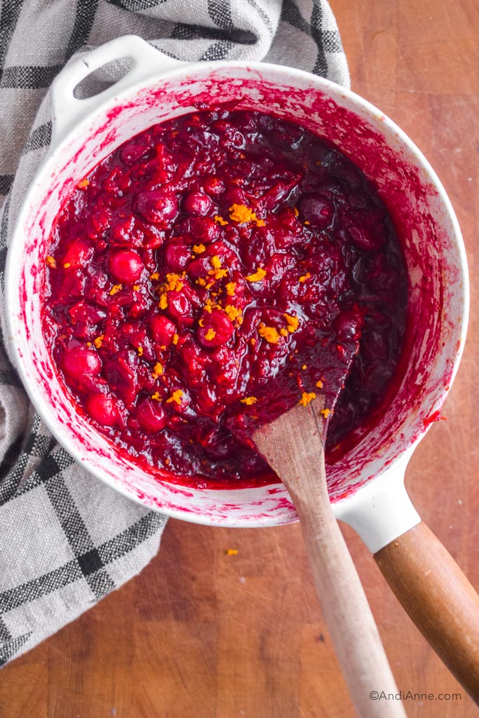 cooked cranberry sauce in a white pot with wooden spoon.