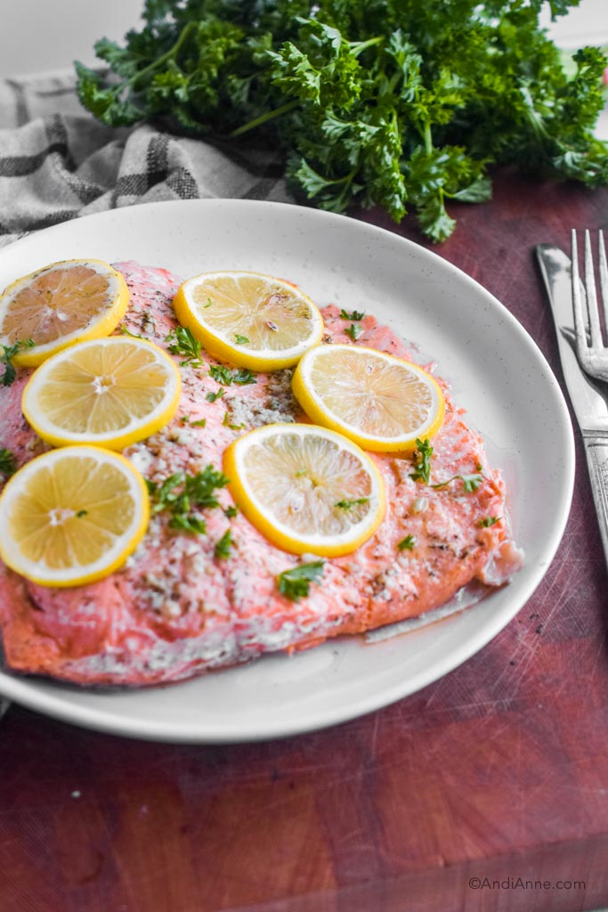 Cooked steelhead trout on a white plate with lemon slices on top. Fork and knife and bunch of parsley surround the plate.