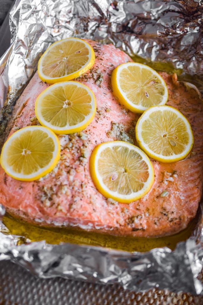 Baked lemon garlic steelhead trout in a buttery sauce inside foil.