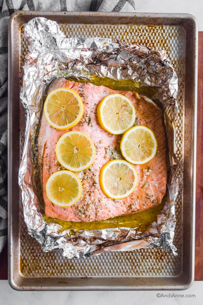 baked steelhead trout in foil with lemon slices on top. All sitting on a baking sheet.