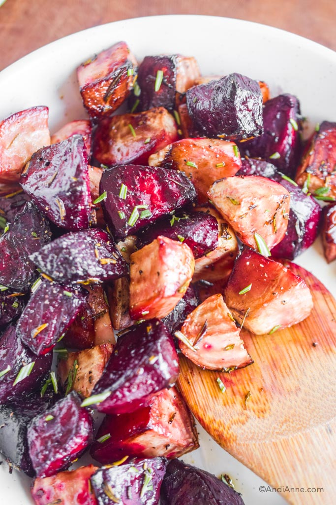 Close detail of cooked red beets and striped beets with a large wooden spoon.