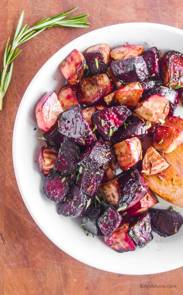 roasted red beets and striped beets in a white bowl with chopped rosemary sprinkled on top.