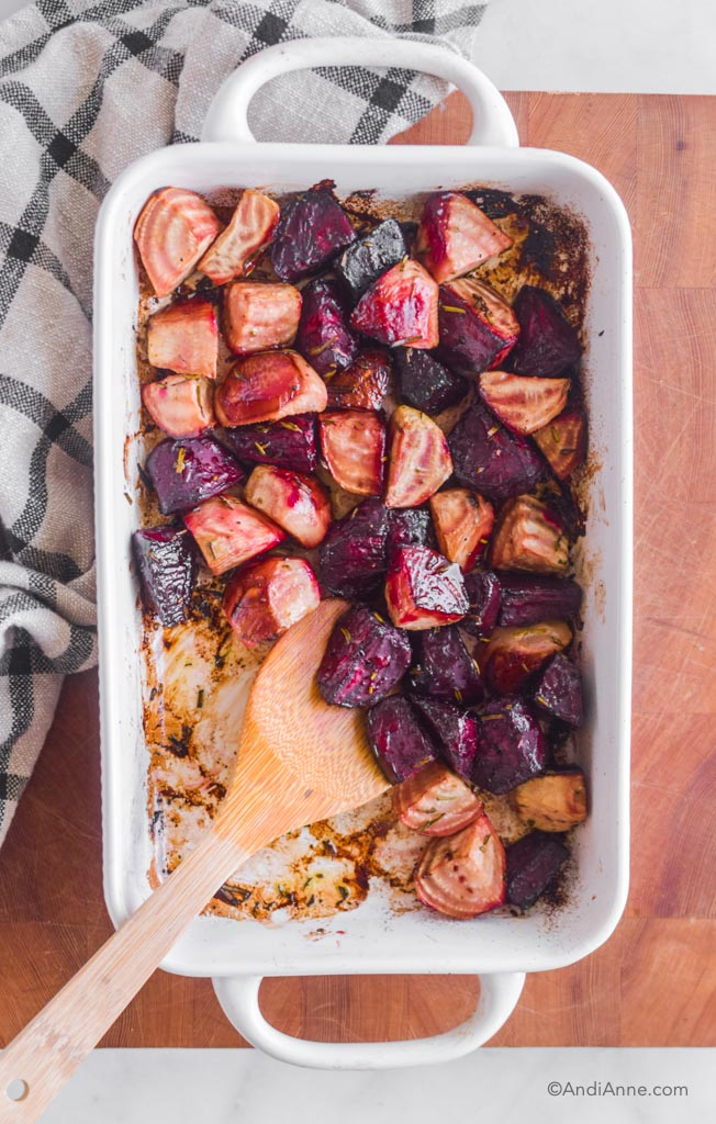 Roasted beets in a white casserole dish with a wooden spoon. A kitchen towel is beside it.
