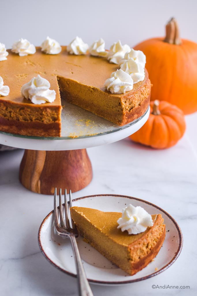 sugar-free pumpkin cheesecake on a cake stand with pumpkins in the background. Slice of cheesecake on a small white plate in the front with a fork.