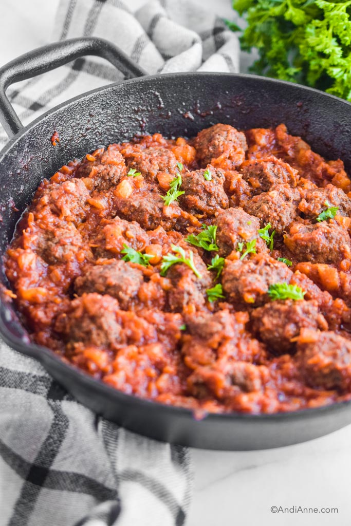 gluten free sweet and sour meatballs in a black skillet with kitchen towel beside it.